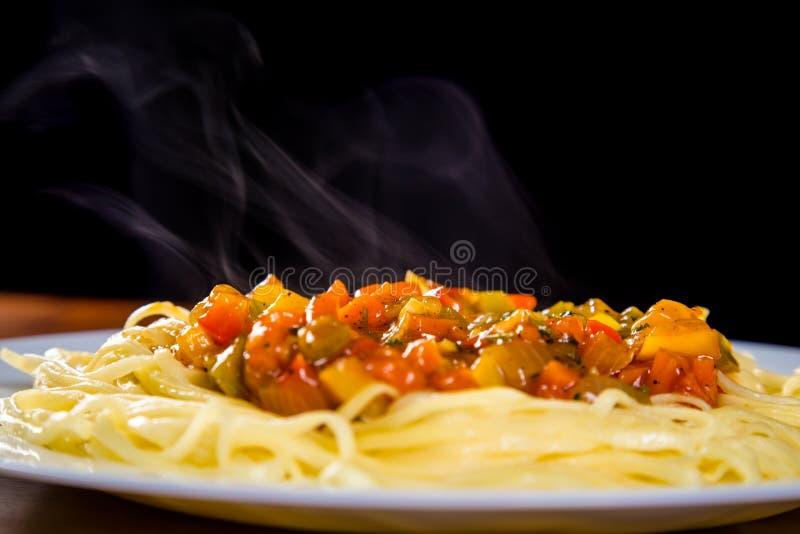 Closeup av nudlar i platta med grönsaksås royaltyfri foto