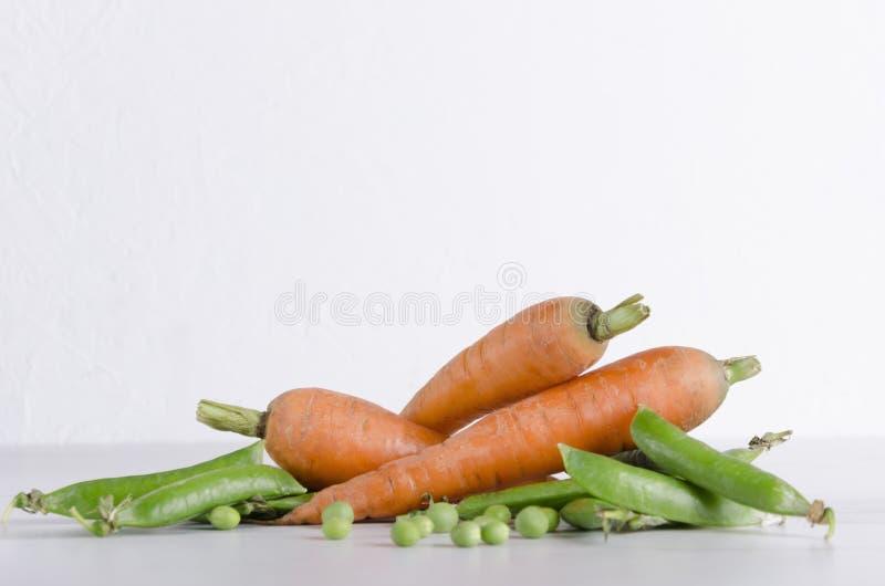 Closeup av nya morötter och gröna unga ärtor i deras fröskidor Sunda ingredienser för strikt vegetarianmeny på den vita tabellen  arkivbilder