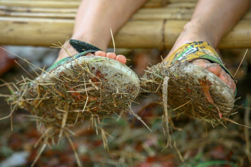 Closeup av par av smutsiga sandaler som är fulla av gyttja och hö som är slitna av en pojke som sitter på en bambubänk arkivbild