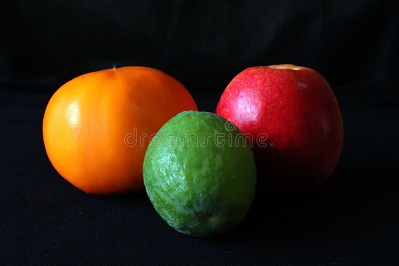 Closeup av persimon-, Apple och Feijoa frukter mot svart bakgrund arkivbilder