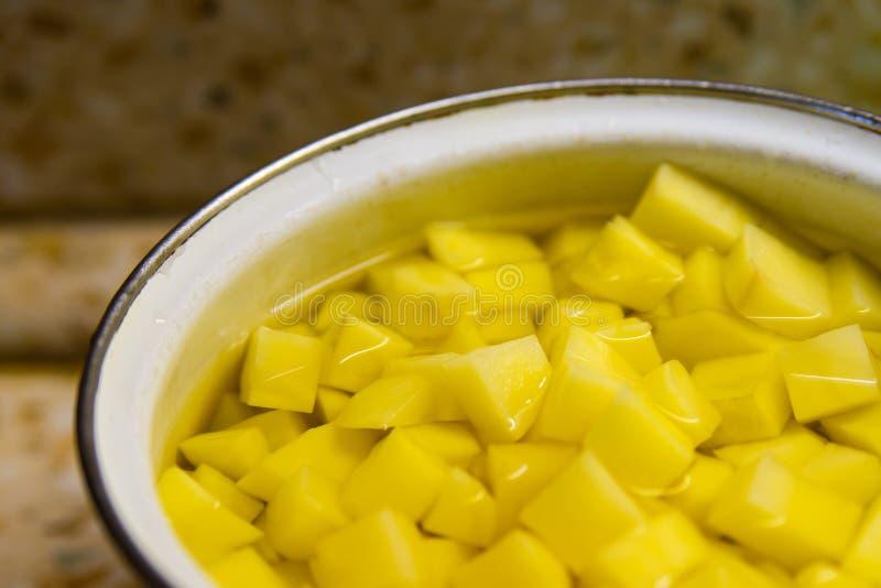 Closeup av potatissnittet i stycken i vatten med den selektiva fokusen arkivfoto