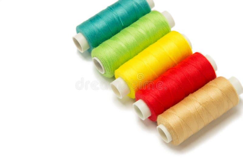 Closeup av röda, gula, guld- och gröna trådar som isoleras på vit bakgrund Hand - gjorda objekt arkivfoto