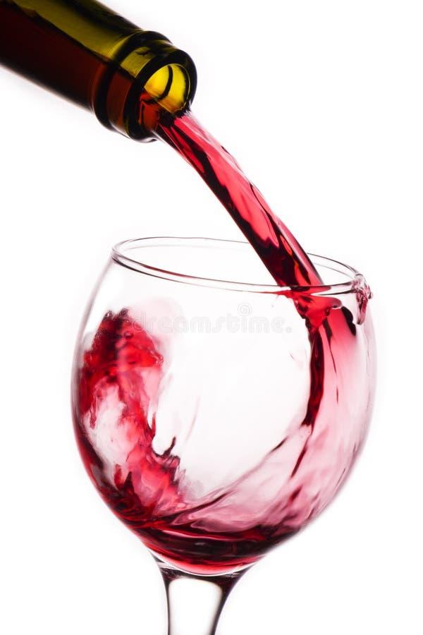 Closeup av rött vin som häller in i exponeringsglas arkivfoton