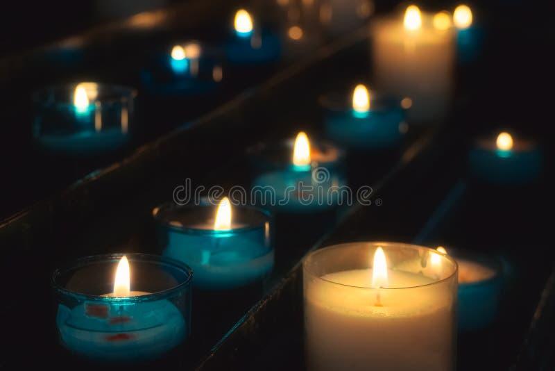 Closeup av rader av bönstearinljus som bränner i blåa exponeringsglastealights i en kyrka arkivbild