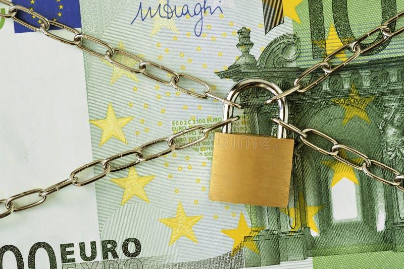 Closeup av sedeln för euro som 100 låsas med kedjan och hänglåset - begrepp av försäkring, ok-i och finansiell säkerhet arkivfoton