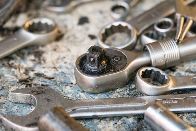 Closeup av spärrhjulskiftnyckeln och skiftnyckeln för öppet slut på tabellen i garage Uttrycka av rött färgar lokaliserat över te royaltyfria foton