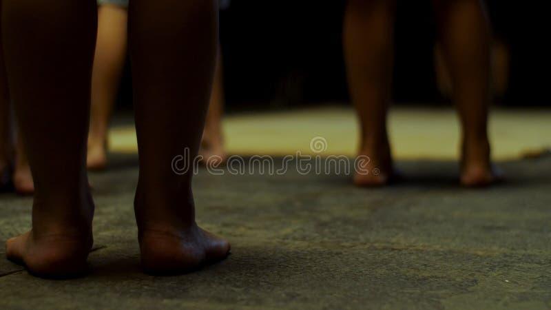 Closeup av svart afrikanskt folk som blir i mörkt rum Nära övre sikt av afrikanska ben på mörk bakgrund royaltyfri fotografi