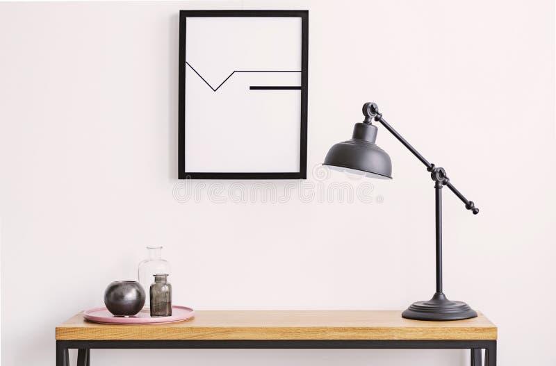 Closeup av tabellen med lampan och plattan med glasflaskor, affisch i svart ram på den vita väggen royaltyfri bild