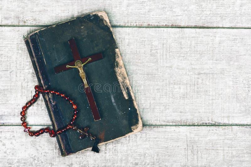 Closeup av träkristenkorset och bibel på den gamla träbakgrunden royaltyfria foton