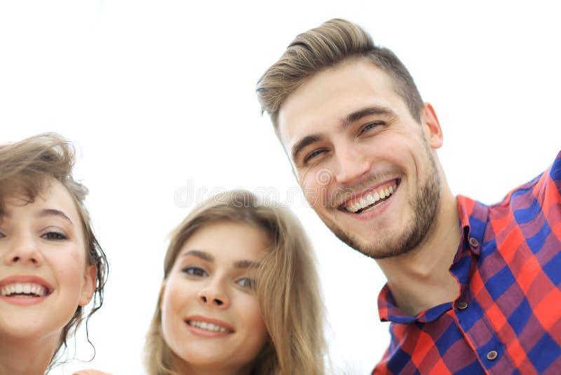 Closeup av tre ungdomarsom ler på vit bakgrund royaltyfria bilder