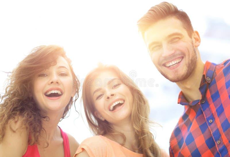 Closeup av tre ungdomarsom ler på vit bakgrund fotografering för bildbyråer