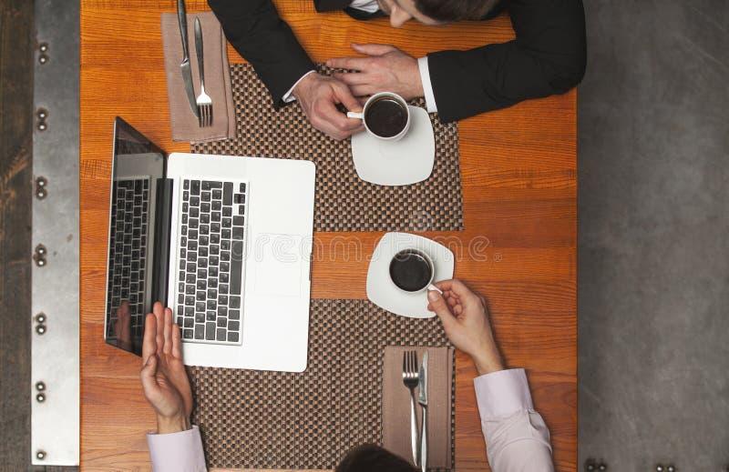 Closeup av två affärsmän som sitter i kafé och använder bärbara datorn royaltyfri bild