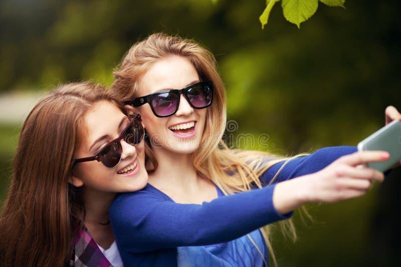 Closeup av två gladlynta vänner som har gyckel arkivfoto