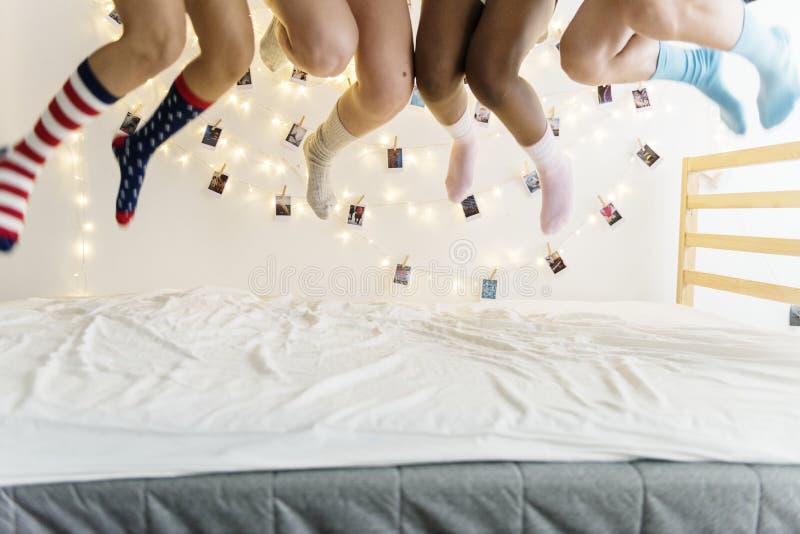 Closeup av två par av ben med sockor som hoppar på sängen arkivbilder