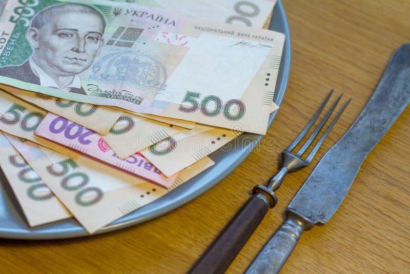 Closeup av ukrainska pengar som ligger p? en platta med en gaffel och en kniv arkivbild