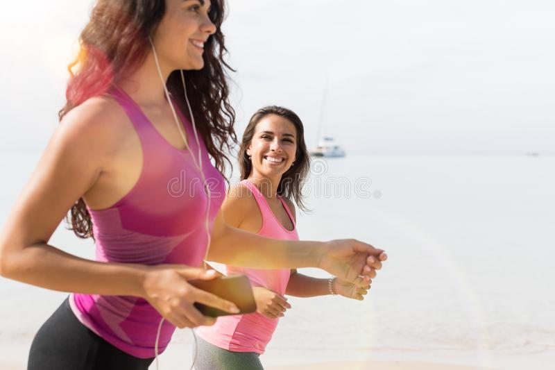 Closeup av ung kvinna som två tillsammans joggar på attraktiva flickor för strand som kör på utbildning för kondition för sjösida royaltyfria foton