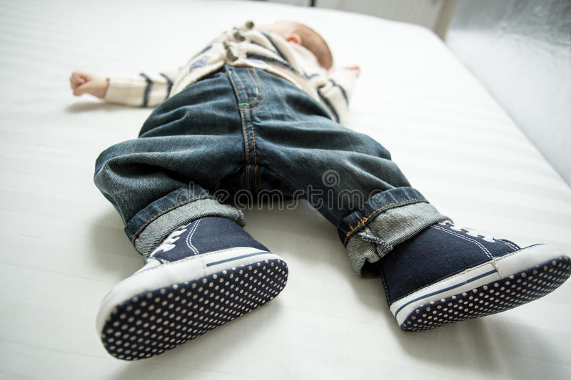 Closeup of baby boy feet in jeans and sneakers lying on bed stock photo