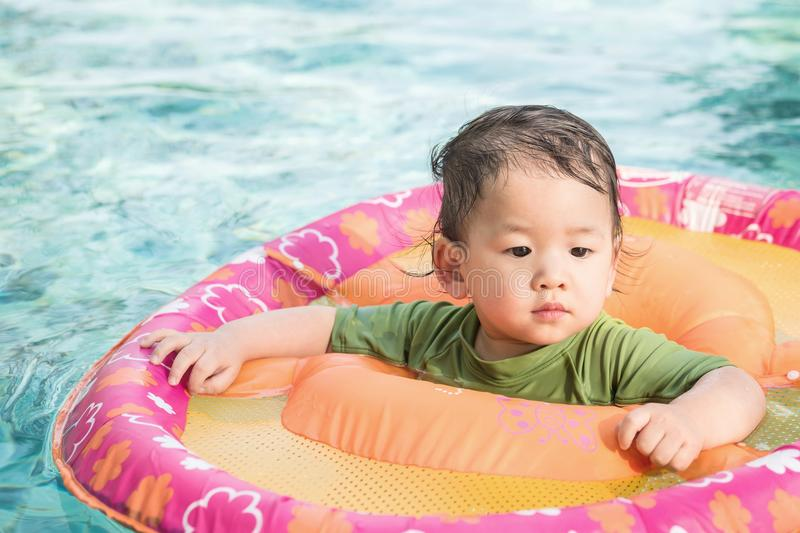 Closeup a baby boy sit in a boat for children in the swimming pool background. Closeup baby boy sit in a boat for children in the swimming pool background stock photography