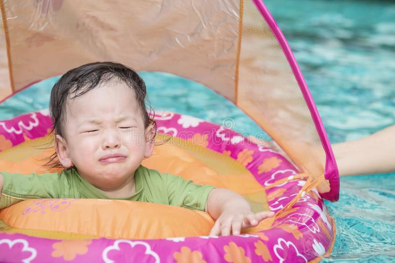 Closeup a baby boy sit in a boat for children in the swimming pool background in fear emotion. Closeup baby boy sit in a boat for children in the swimming pool stock photo
