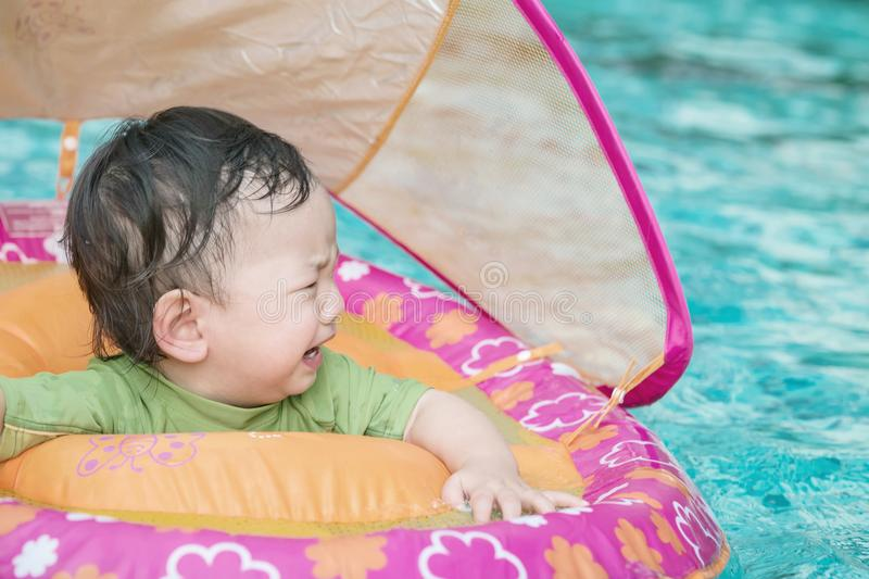 Closeup a baby boy sit in a boat for children in the swimming pool background in fear emotion. Closeup baby boy sit in a boat for children in the swimming pool stock photos
