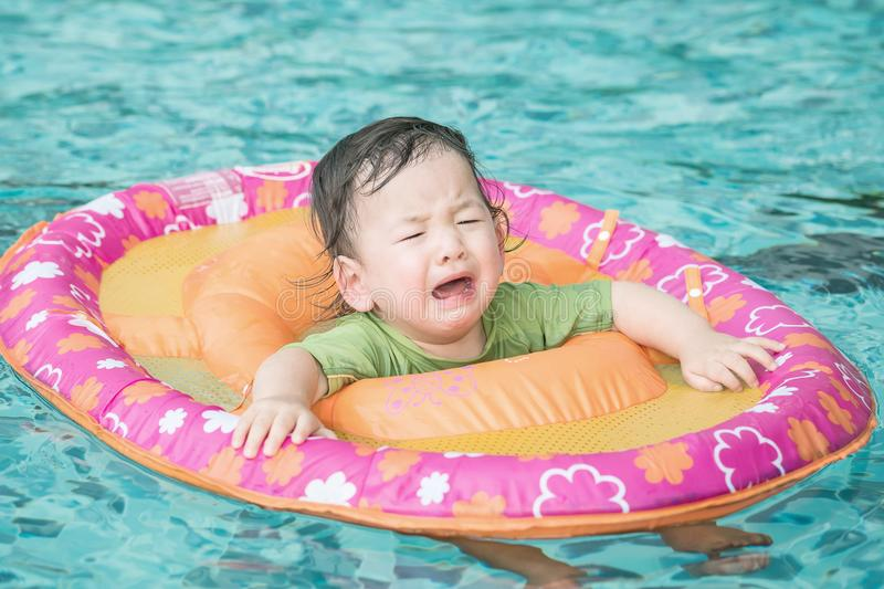 Closeup a baby boy sit in a boat for children in the swimming pool background in fear emotion. Closeup baby boy sit in a boat for children in the swimming pool royalty free stock photography