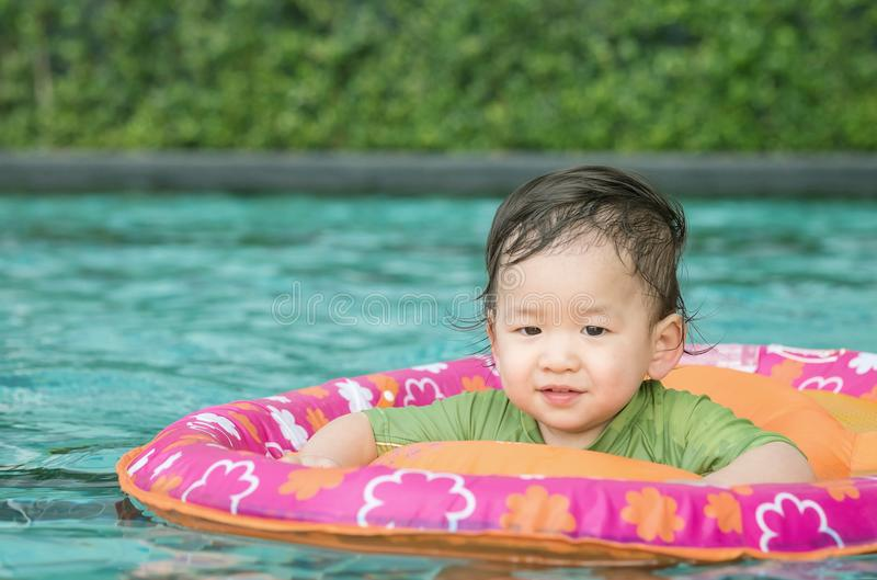 Closeup a baby boy sit in a boat for children in the swimming pool background with smile face in happy emotion. Closeup baby boy sit in a boat for children in royalty free stock photos