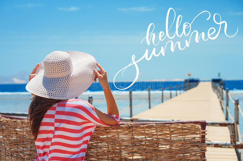 Closeup back view of woman in white hat looking out towards blue ocean and sky and words Hello summer. Calligraphy. Lettering stock photos