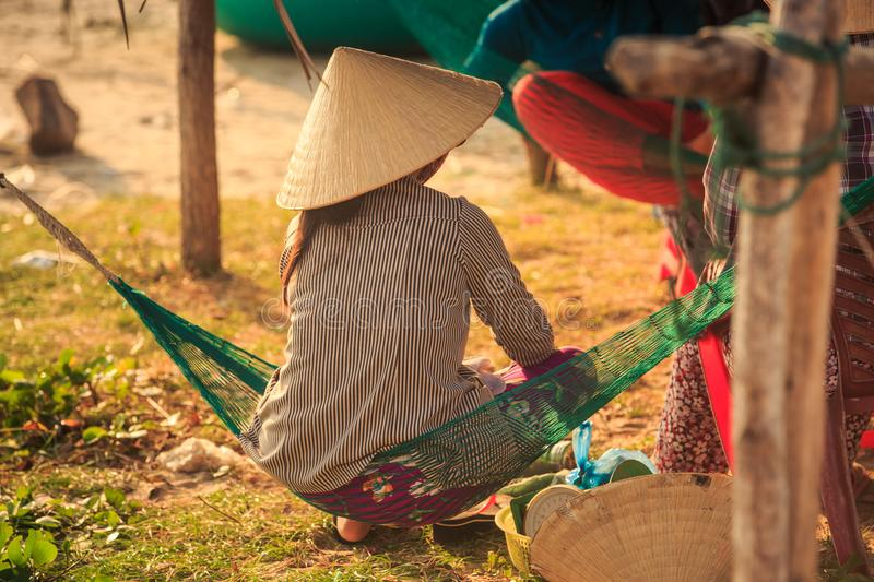 Backside Woman in Straw Hat Sits in Hammock in Vietnam. Closeup backside view Vietnamese woman in national straw hat sits in small hammock in backyard stock photography