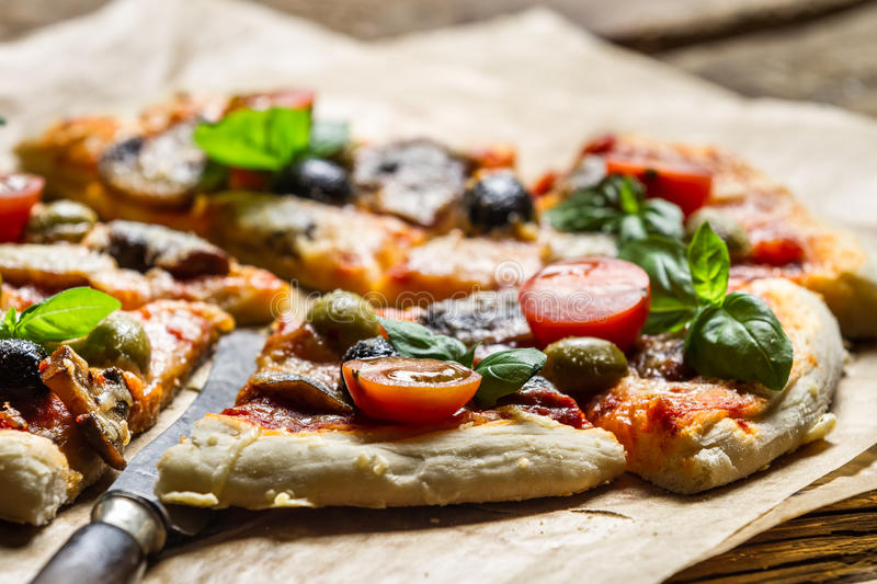 Closeup of baked pizza with olives and tomatoes stock photo