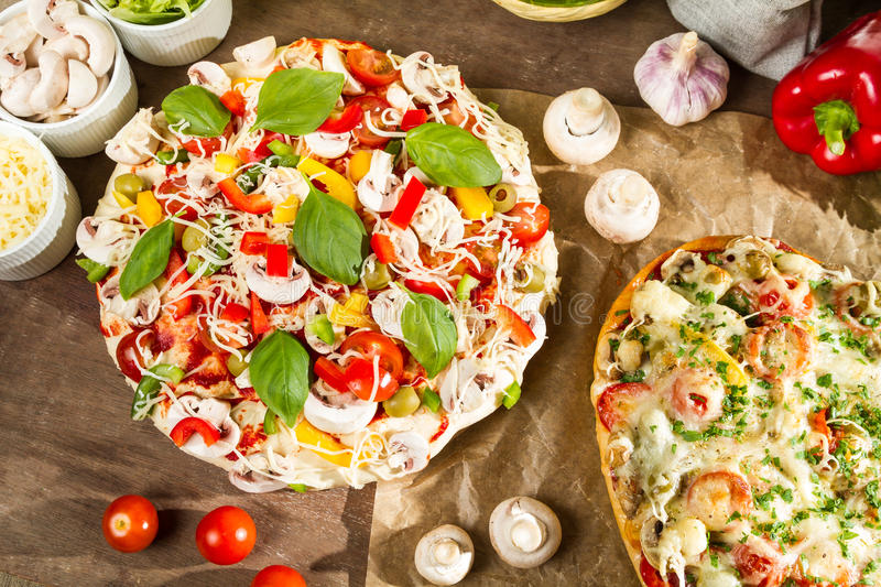 Closeup of baked and raw pizza royalty free stock images