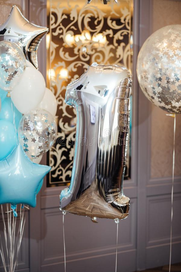 Anniversary or birthday photo zone with white, blue and transparent balloons, free space. Colorful balloons background, one year. royalty free stock image