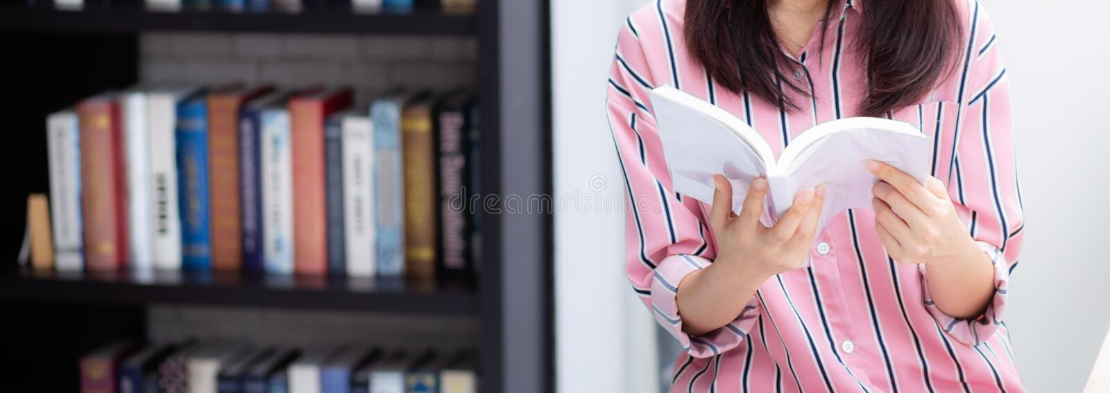 Closeup banner website young asian woman relax sitting reading book in living room at home stock photography