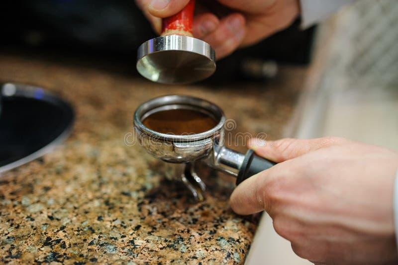 Closeup barista grinding fresh coffee. Into bayonet stock photo