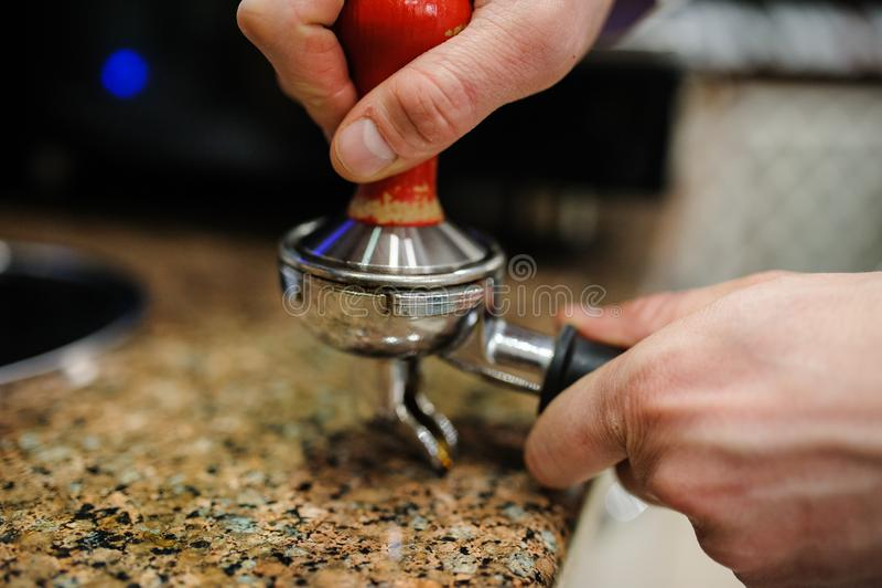Closeup barista grinding fresh coffee. Into bayonet stock image