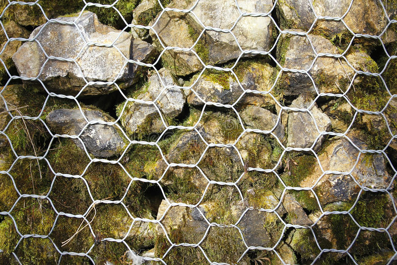 Closeup of a barrier built of small pieces of rock behind a fence of metallic mesh royalty free stock photography