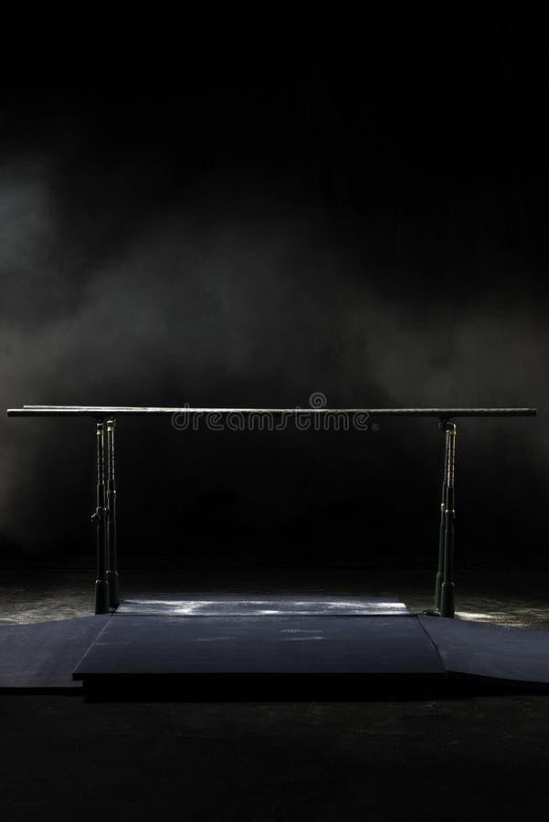 closeup bars gymnastisk parallel Isolerat på svart bakgrund med dimma, lodlinjeskott royaltyfri bild