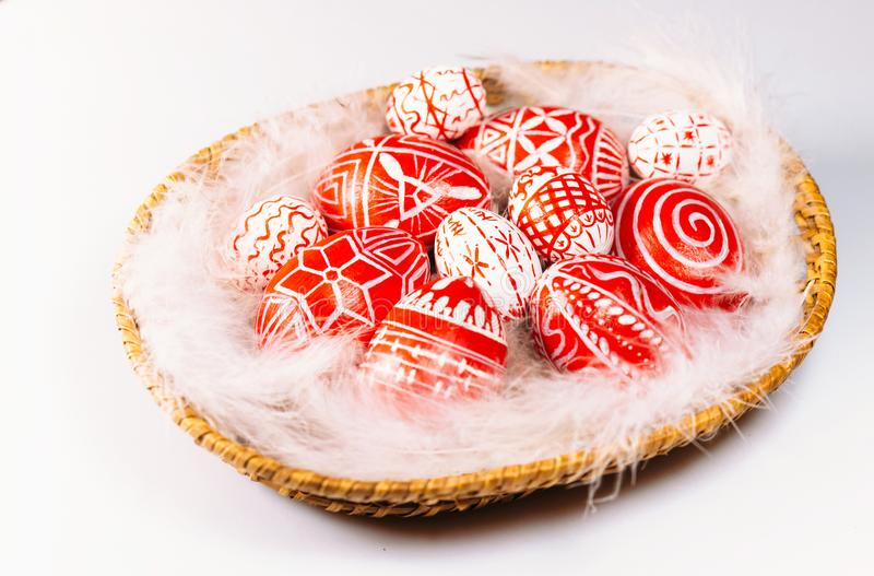 Closeup basket with Easter red eggs with folk white pattern lay on feather on white background. Ukrainian traditional eggs royalty free stock photos