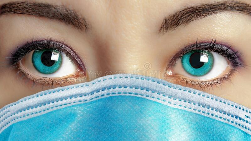 Closeup of beautiful blue eyes woman face wearing surgical mask to protect her from getting ill. Virus protection royalty free stock photography