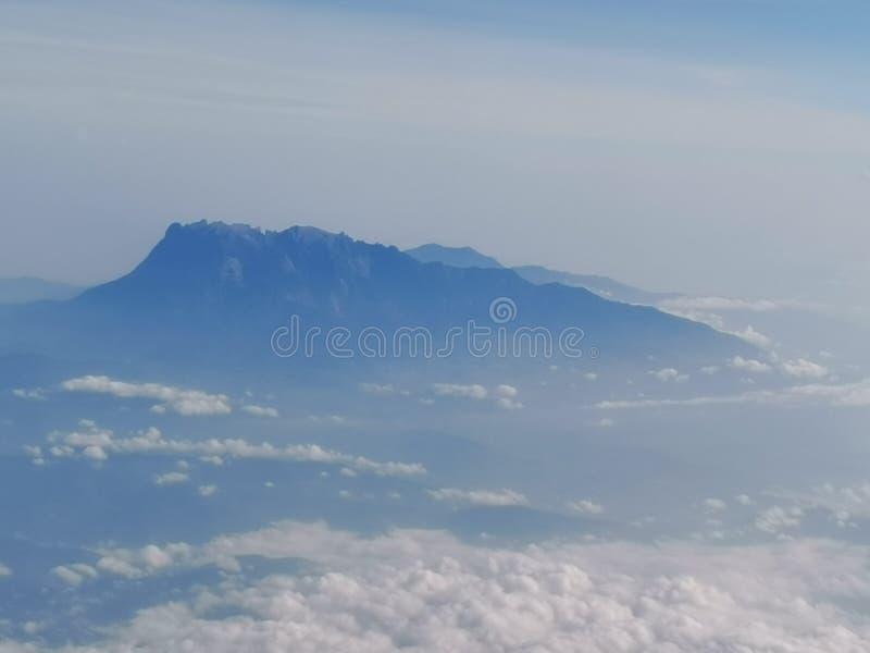 Closeup with beautiful blue sky and the stunning Mount Kinabalu view  looking through the window aircraft.Sabah, Malaysia. Borneo. royalty free stock photography