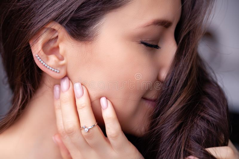 Closeup beautiful brunette girl with long hair in modern silver jewelry earrings, rings, bracelet, chain, necklace. Ð¡oncept. Shooting for store gentle stock image