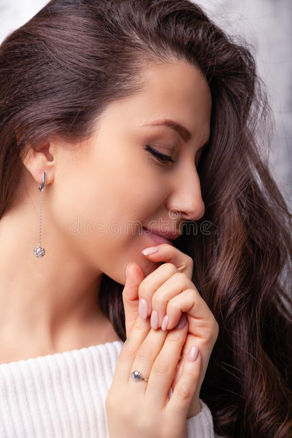 Closeup beautiful brunette girl with long hair in silver jewelry earrings, rings, bracelet, chain, necklace. Ð¡oncept shooting. For jewelry store gentle royalty free stock image
