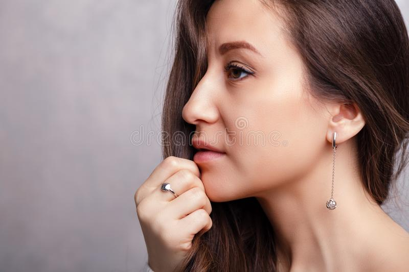 Closeup beautiful brunette girl with long hair in silver jewelry earrings, rings, bracelet, chain, necklace. Ð¡oncept shooting. For jewelry store gentle royalty free stock photo
