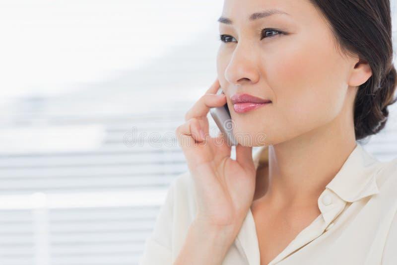 Closeup of a beautiful businesswoman using cellphone stock photography
