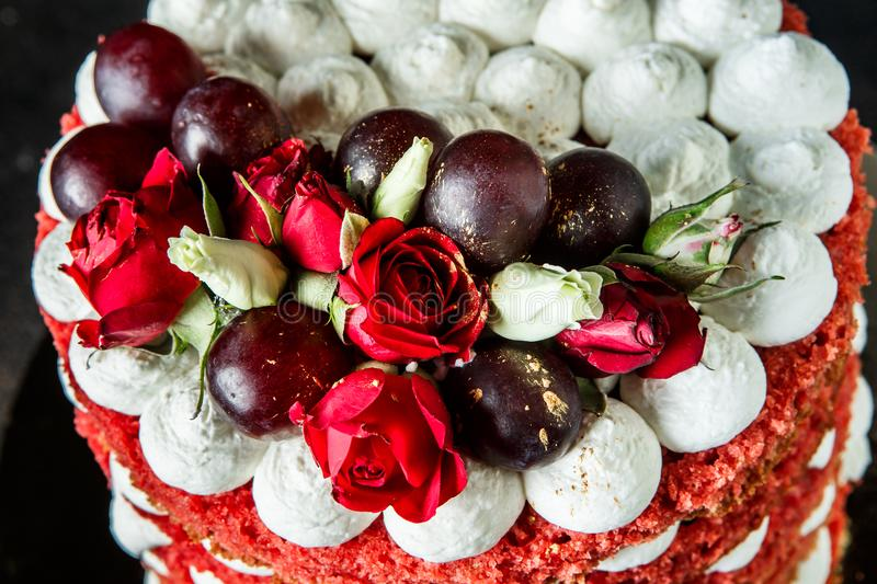 Closeup beautiful cake with bizet, grapes and roses top view. Closeup of beautiful multi-layer cake with white bizet, grapes and red and white roses top view royalty free stock images