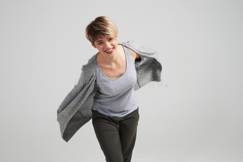 Girl with short haircut in the flowing cardigan posing at studio stock image