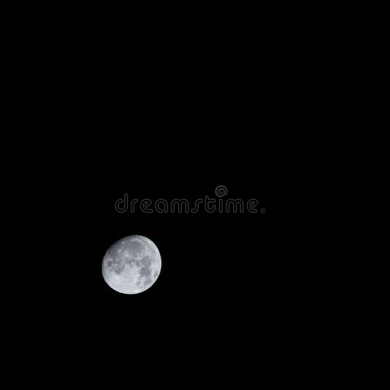 Closeup of the beautiful grey moon in the pitch black dark sky royalty free stock image