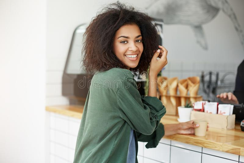 Close up of beautiful joyful african student girl with dark wavy hair in green cardigan sitting in cafe, drinking cup of stock photography