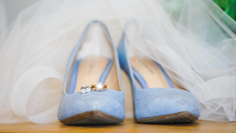 Closeup of beautiful light blue female wedding shoes under a white wedding dress royalty free stock photos
