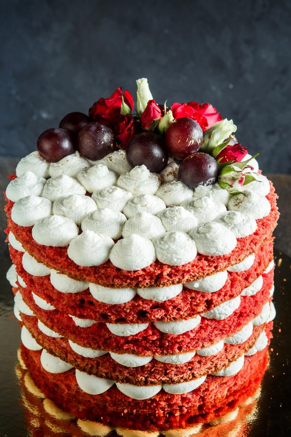Closeup beautiful cake with bizet, grapes and roses. Closeup beautiful multi-layer cake with white airy bizet, red grapes and red and white roses royalty free stock photo