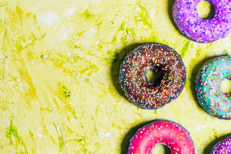 Closeup of beautiful multicolored sweet donuts in a plate on blue grunge background with copy space. stock photography